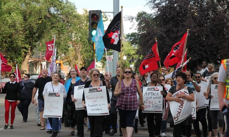 "AUPE members participate in an info-picket in 2019, marching together and holding signs which say ""fighting for public health care,"" ""proud of my job; ashamed of the government,"" ""attack our wage feel our rage,"" and ""solidarity!"" Some are also holding AUPE flags."